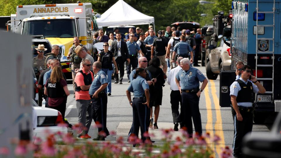 Law enforcement officials survey the scene after a gunman fired through a glass door at the Capital Gazette newspaper and sprayed the newsroom with gunfire, killing at least five people and injuring several others in Annapolis, Maryland, US, June 28, 2018.