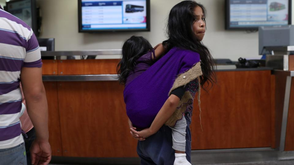 A Guatemalan mother and her two-year-old daughter are released from detention with fellow undocumented immigrant families at a bus depot in McAllen, Texas, US, July 3, 2018.