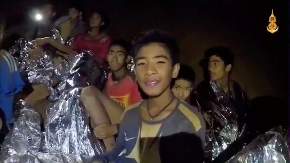 Boys from the under-16 soccer team trapped inside Tham Luang cave covered in hypothermia blankets react to the camera in Chiang Rai, Thailand, in this still image taken from a July 3, 2018 video by Thai Navy Seal.