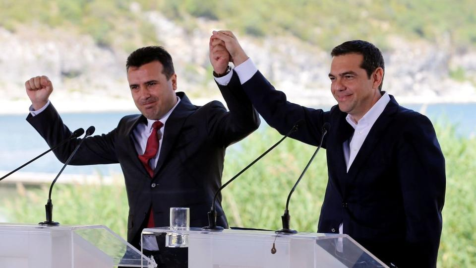 Greek Prime Minister Alexis Tsipras, right, and Macedonian Prime Minister Zoran Zaev join hands before the signing of an accord to settle a long dispute over the former Yugoslav republic's name, in the Greek village of Psarades on June 17, 2018.