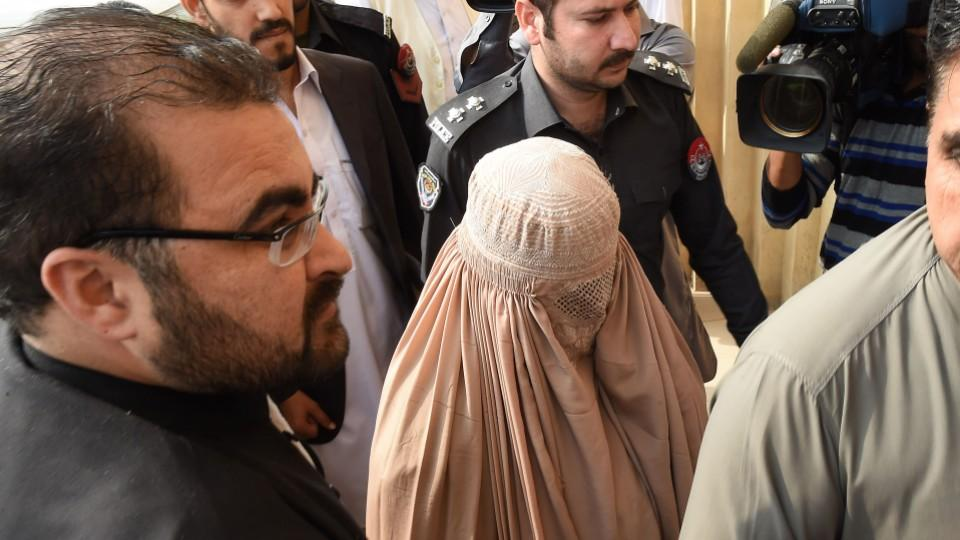 """Sharbat Gula, the woman known as the """"Afghan Girl,"""" leaves a courthouse in Peshawar, Pakistan on November 4."""