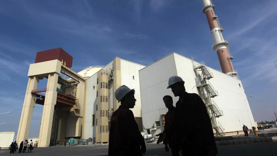 Iranian workers stand in front of the Bushehr nuclear power plant, about 1,200 km (746 miles) south of Tehran October 26, 2010.