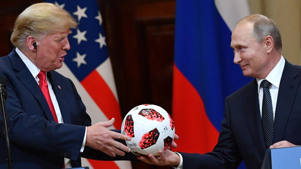 Russia's President Vladimir Putin (R) offers a ball of the 2018 football World Cup to US President Donald Trump during a joint press conference after a meeting at the Presidential Palace in Helsinki, on July 16, 2018.