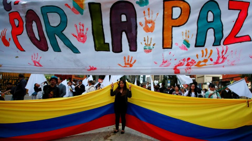 """Supporters rallying for the nation's new peace agreement with FARC stand under a banner reading """"for peace"""" during a march in Bogota, Colombia."""