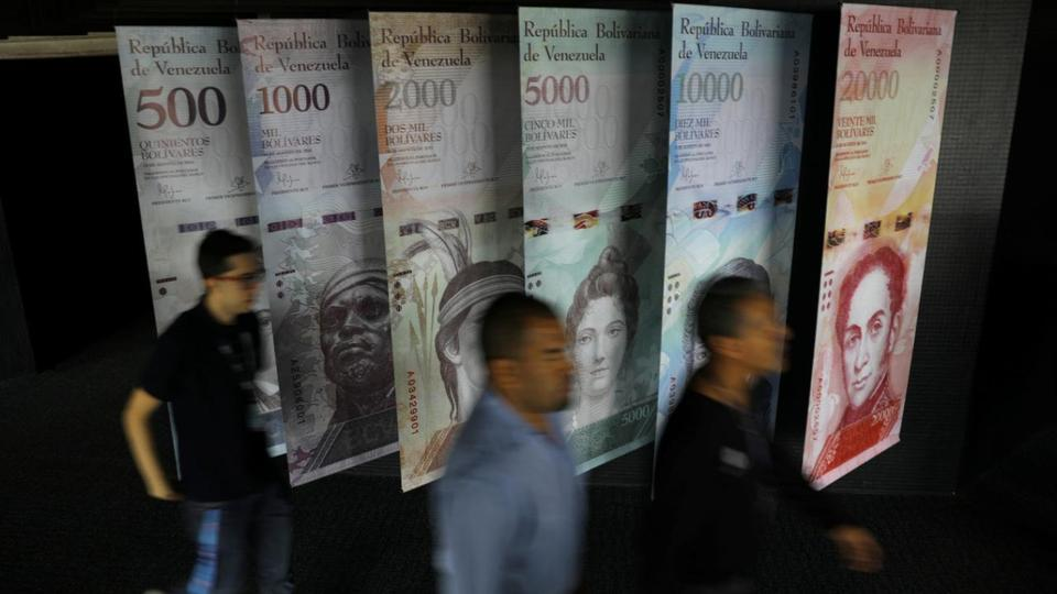 People walk by banners of Venezuelan bolivar notes displayed at the Venezuelan Central Bank building in Caracas, Venezuela May 23, 2017.
