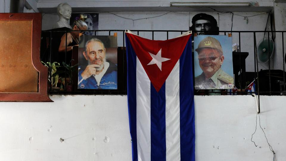 The Cuban flag hangs next to the photographs of late Cuba's President Fidel Castro and his brother, Cuba's former President Raul Castro, in Havana, Cuba July 21, 2018.