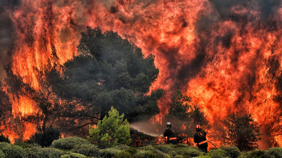 Firefighters try to extinguish flames during a wildfire at the village of Kineta, near Athens, on July 24, 2018.