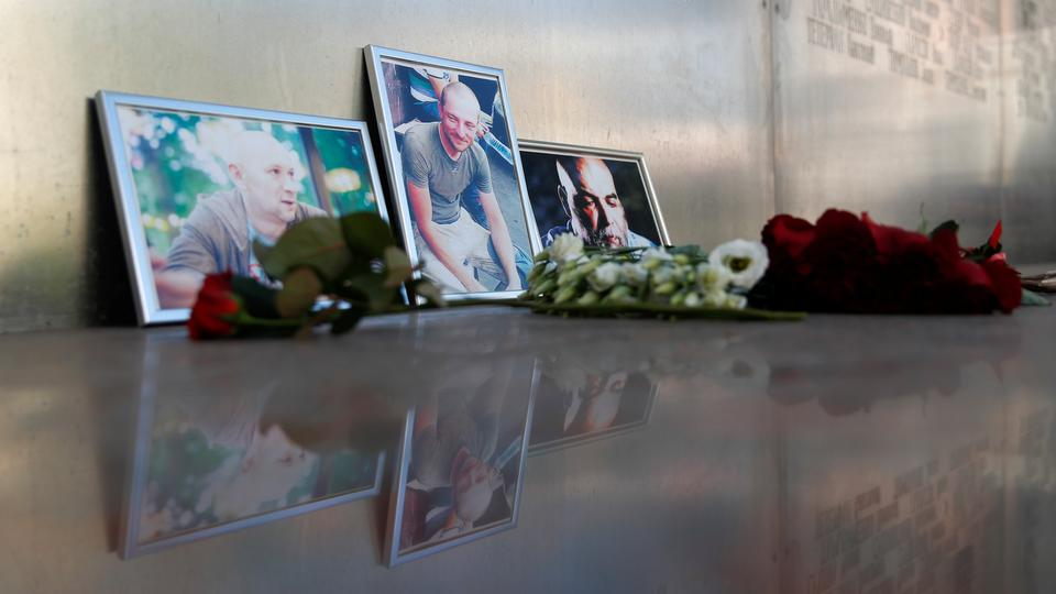 Photographs of journalists, (R-L) Orhan Dzhemal, Kirill Radchenko and Alexander Rastorguyev, who were recently killed in Central African Republic by unidentified assailants, on display outside the Central House of Journalists in Moscow, Russia August 1, 2018.