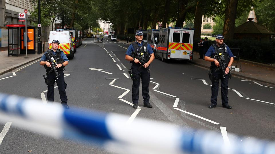 Armed police officers stand at a cordon after a car crashed outside the Houses of Parliament in Westminster, London, Britain. August 14, 2018.