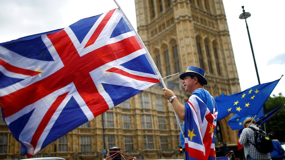 Anti-Brexit demonstrators wave EU and Union flags opposite the Houses of Parliament, in London, Britain on June 19, 2018.