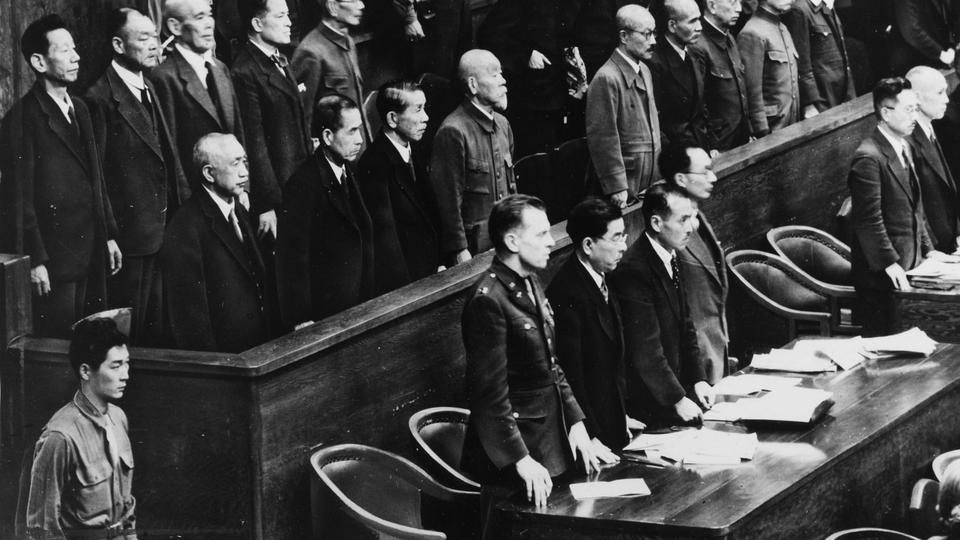 Former Japanese premier Hideki Tojo, (5th from left in the prisoners' dock) and other Japanese war leaders stand to hear the sentence of death in the war crimes trial in Tokyo. Unlike the Nuremberg tribunal,  the IMTFE or the Far East tribunal was not created by a formal international agreement but a special proclamation by General MacArthur, the supreme commander of the Allied Powers, to try Japanese war criminals. January 1, 1948.
