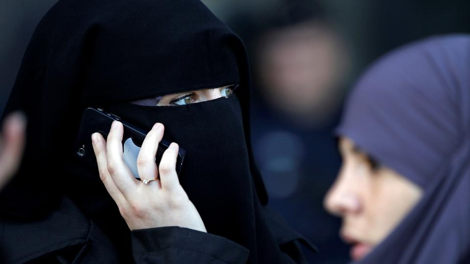 A women, wearing a niqab despite a nationwide ban on the Islamic face veil, gives a phone call outside the courts in Meaux, east of Paris, September 22, 2011. (File photo)