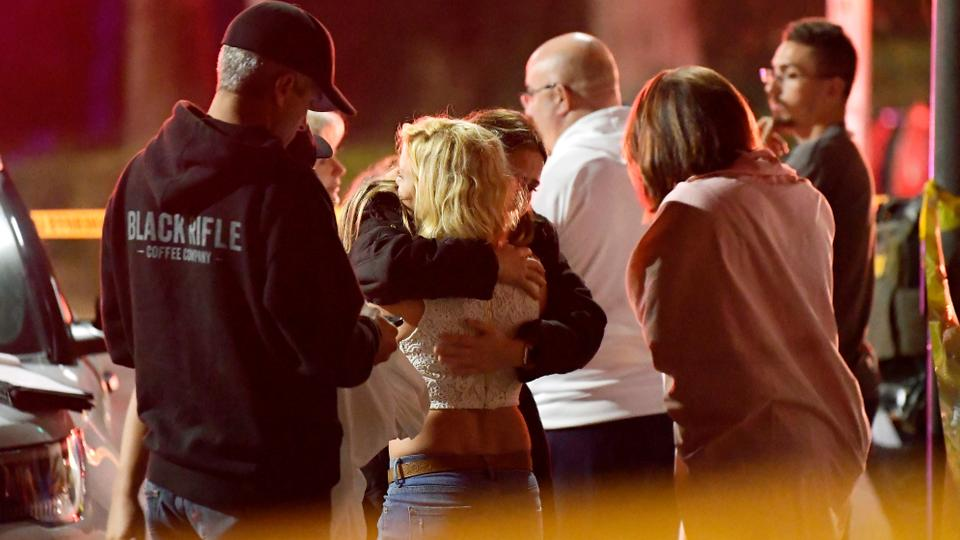 People comfort each other as they stand near the shooting scene in Thousand Oaks, California.