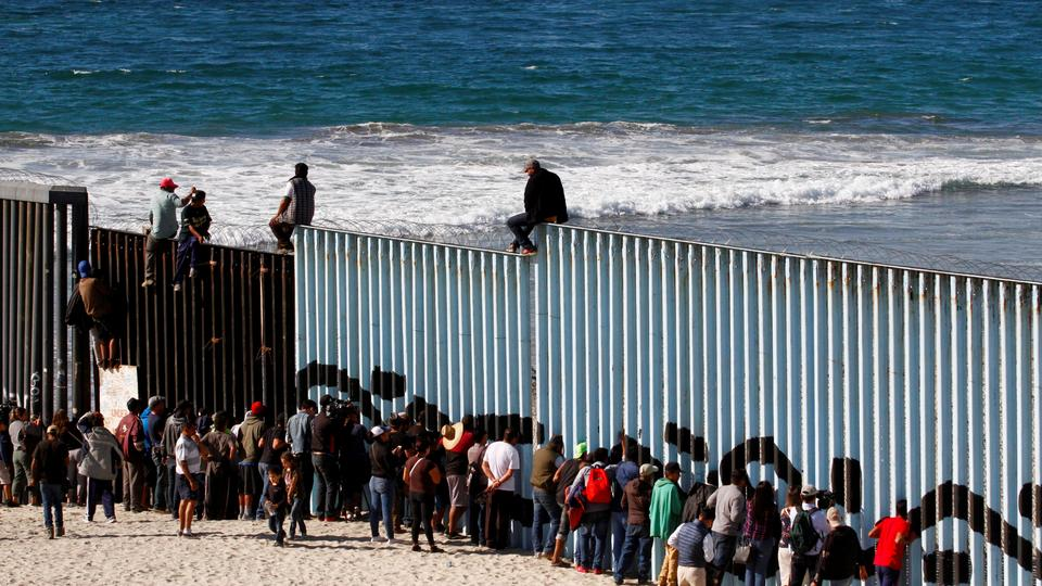 Migrants, part of a caravan of thousands trying to reach the US, look through the border fence between Mexico and the United States, in Tijuana, Mexico November 14, 2018.