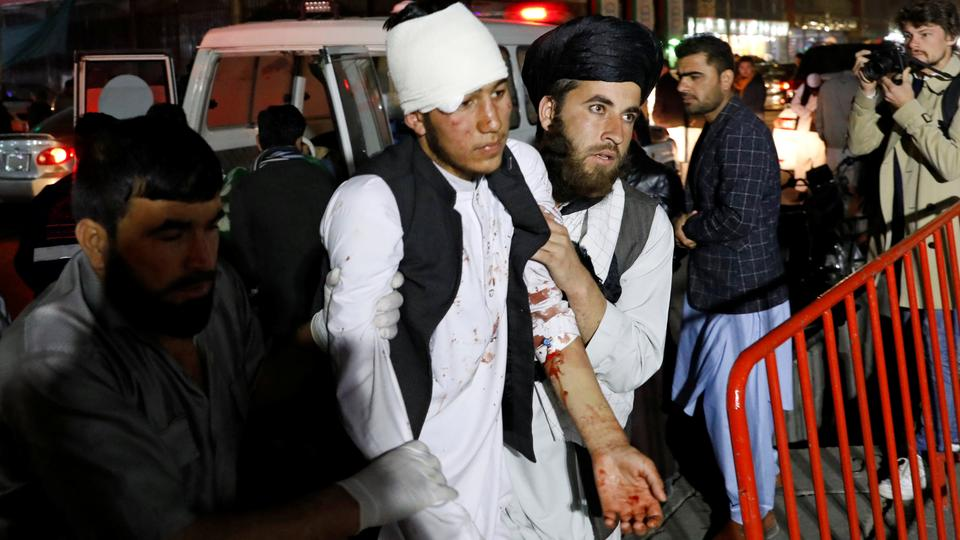 Afghan men carry a wounded person to a hospital after a suicide attack in Kabul, Afghanistan November 20, 2018.