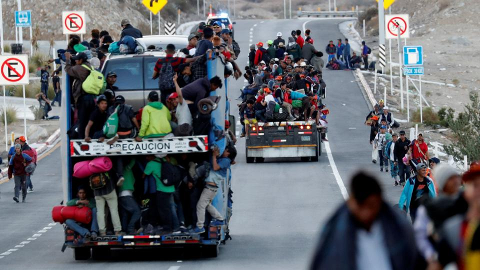 Migrants, part of a caravan of thousands travelling from Central America en route to the United States, sit on the back of a truck while making their way to Tijuana from Mexicali, in Mexicali, Mexico. (November 20, 2018)