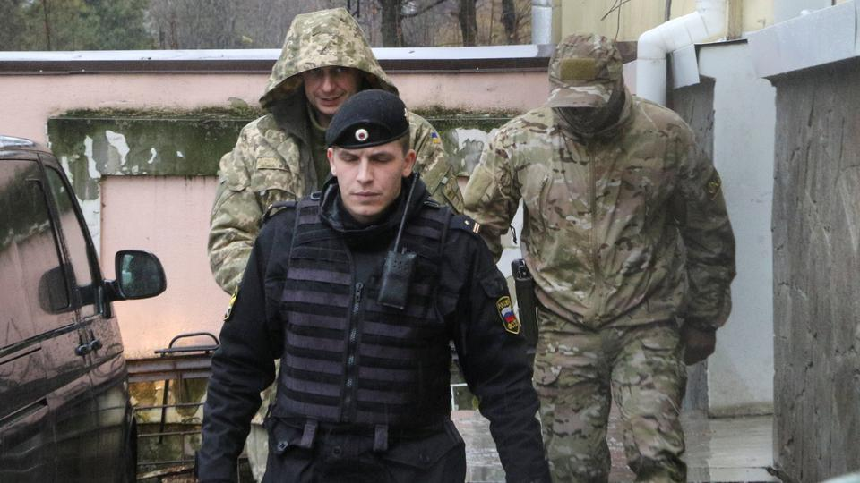 A crew member (L, back) of one of the Ukrainian naval ships, which were recently seized by Russia's FSB security service, is escorted after a court hearing in Simferopol, Crimea, November 28, 2018.