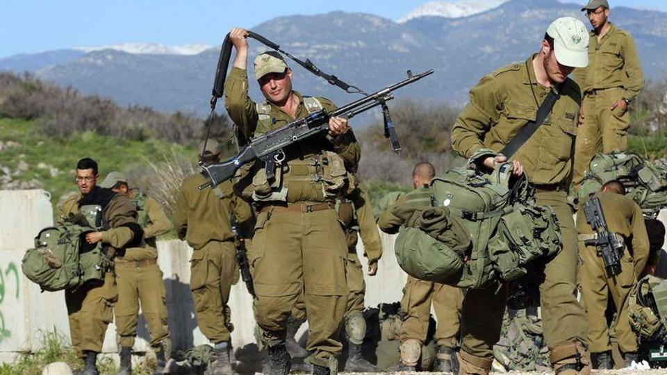 Israeli soldiers carry their belongings in an area near the Israel-Lebanon border on January 29, 2015.