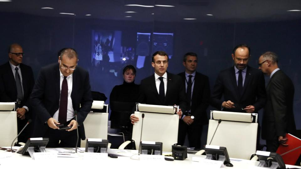 French President Emmanuel Macron (C) presides over an emergency crisis meeting with French Prime Minister Edouard Philippe (center R), French junior Minister for Interior Laurent Nunez (center L) at the Interior Ministry in Paris, France, late 11 December 2018.