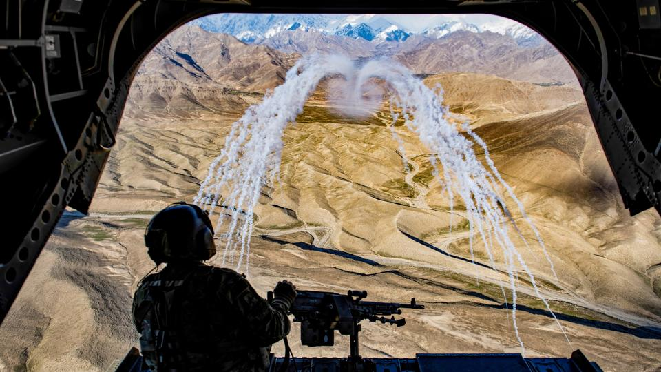 A US army crew chief flying on board a CH-47F Chinook helicopter observes the successful test of flares during a training flight in Afghanistan, on March 14, 2018.