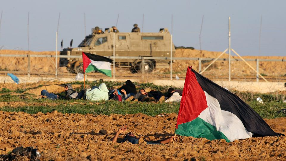 Demonstrators with Palestinian flags take cover as Israeli soldiers are seen on their military vehicle during a protest at the Israel-Gaza border fence, in the southern Gaza Strip, December 21, 2018.