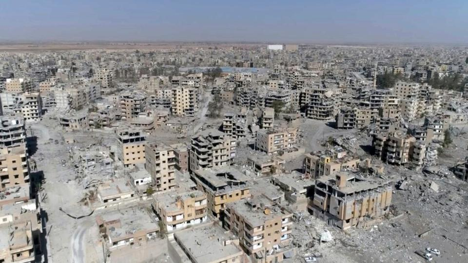 File photo, an image made from drone video shows damaged buildings in Raqqa, Syria, October 19, 2017.