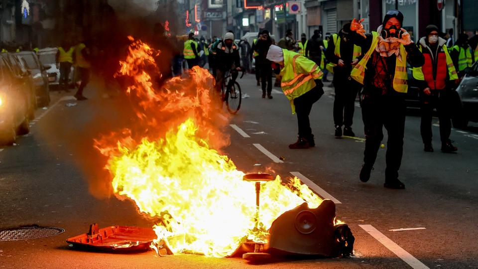 Protestors walk by a burning trash can during a Yellow Vest anti-government demonstration in Lille, northern France, on January 5, 2019.