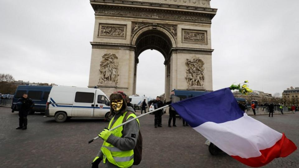 A protester wearing a Guy Fawkes mask and a yellow vest (gilet jaune), holds a French flag in front of the Arc de Triomphe during an anti-government demonstration called by the Yellow Vest movement in Paris, on January 12, 2019.