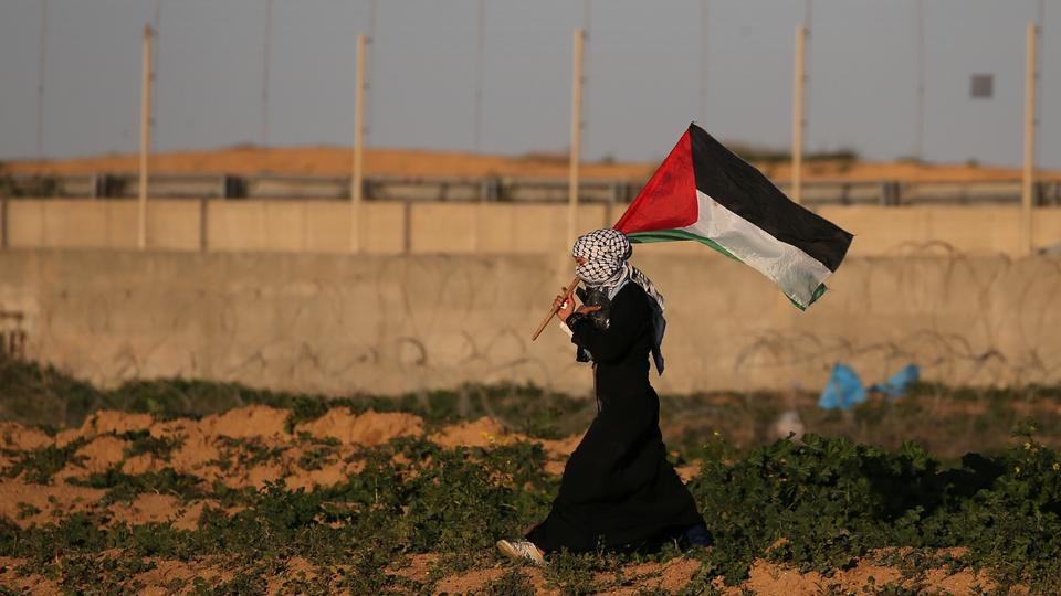 A demonstrator holds a Palestinian flag during a protest near the Gaza-Israel buffer zone, in  southern Gaza on January 18, 2019.