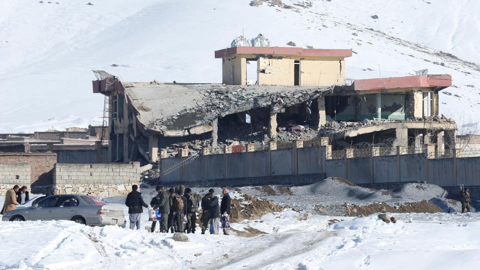 Afghan men stand in front of a collapsed building of a military base after a car bomb attack in Maidan Wardak, Afghanistan, January 21, 2019.