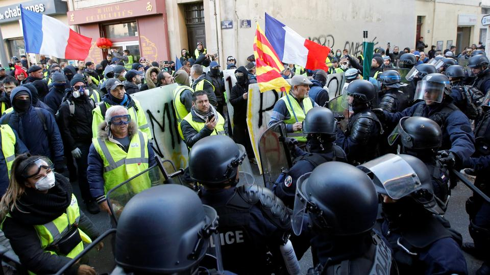 Police officers are seen in front of protesters wearing yellow vests during a demonstration of the Yellow Vests movement in Marseille, France, January 19, 2019.