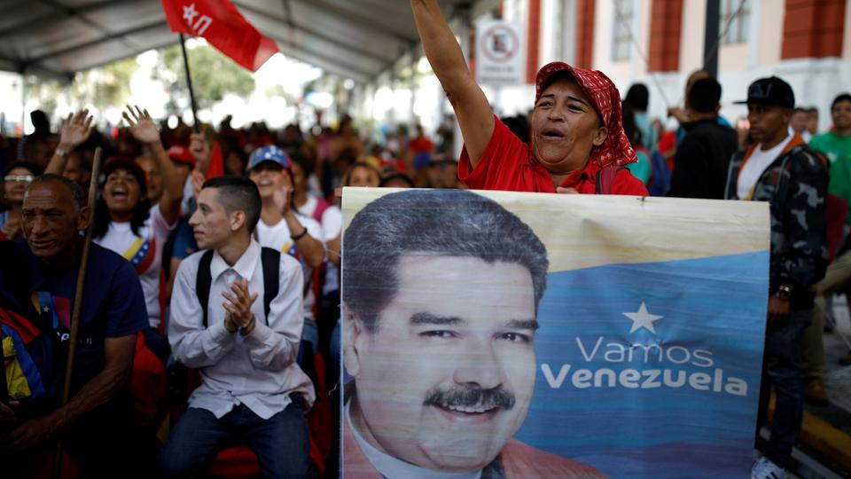 A supporter of Venezuela's President Nicolas Maduro holds a banner depicting him as he takes part in a gathering outside the Miraflores Palace in Caracas, Venezuela January 26, 2019.
