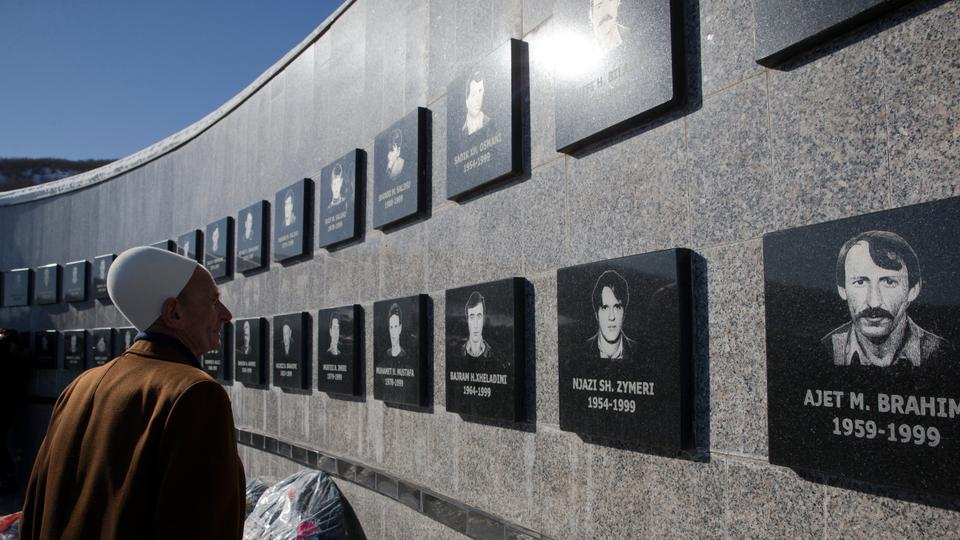 Kosovo Albanian Limon Hajdini visits the commemorative wall dedicated to the victims of the Recak massacre in the village of Recak, Kosovo on Tuesday, Jan. 15, 2019.
