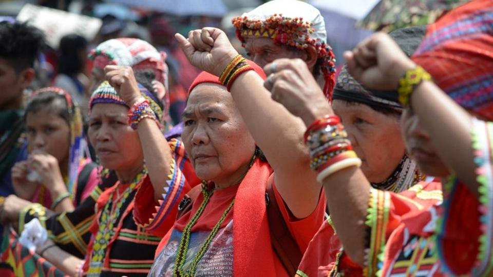 Activists from an indigenous group raise clenched fists during a protest near Malacanang palace to commemorate International Women's Day in Manila on March 8, 2019.