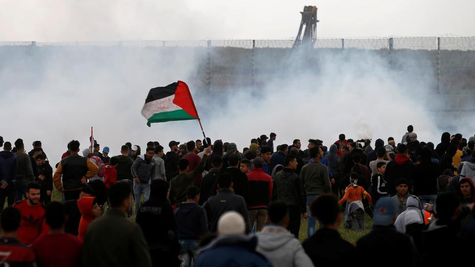 Palestinians gather as tear gas is fired by Israeli forces during a protest marking Land Day and the first anniversary of a surge of border protests, at the Israel-Gaza border fence east of Gaza City, March 30, 2019.
