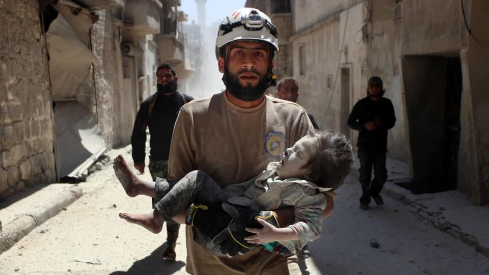 A rescue worker from the White Helmets carries an injured child following an air strike in Syria.