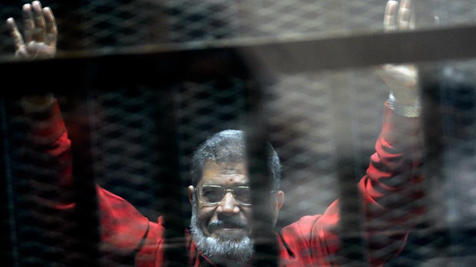 In this June 21, 2015 file photo, former Egyptian President Mohamed Morsi, wearing a red jumpsuit that designates he has been sentenced to death, raises his hands inside a defendant's cage in a makeshift courtroom in Cairo, Egypt.
