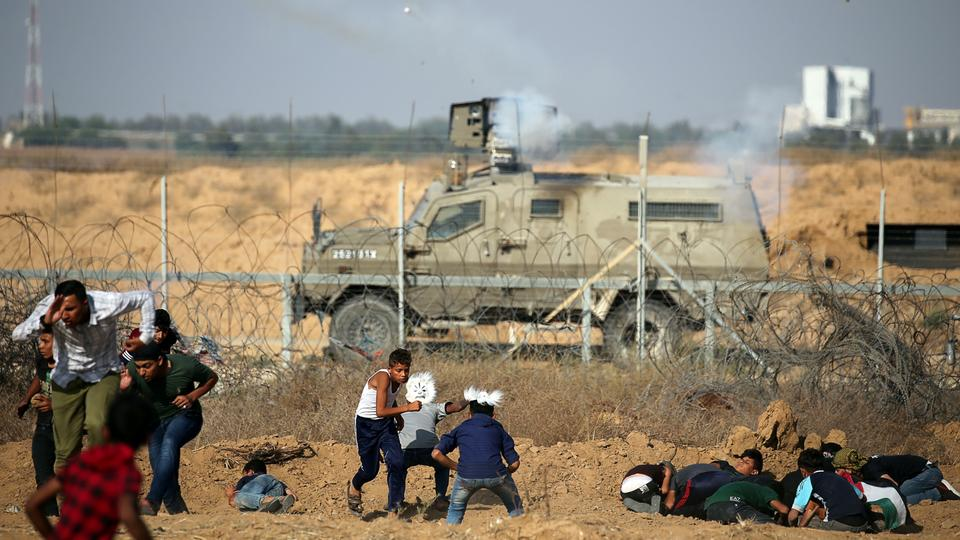 Palestinians run for cover from Israeli gunfire and tear gas during a protest at the Israel-Gaza fence, in the southern Gaza, June 21, 2019.