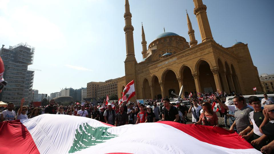 Demonstartors holds a Lebanese flag during an anti-government protest in downtown Beirut, Lebanon October 21, 2019.