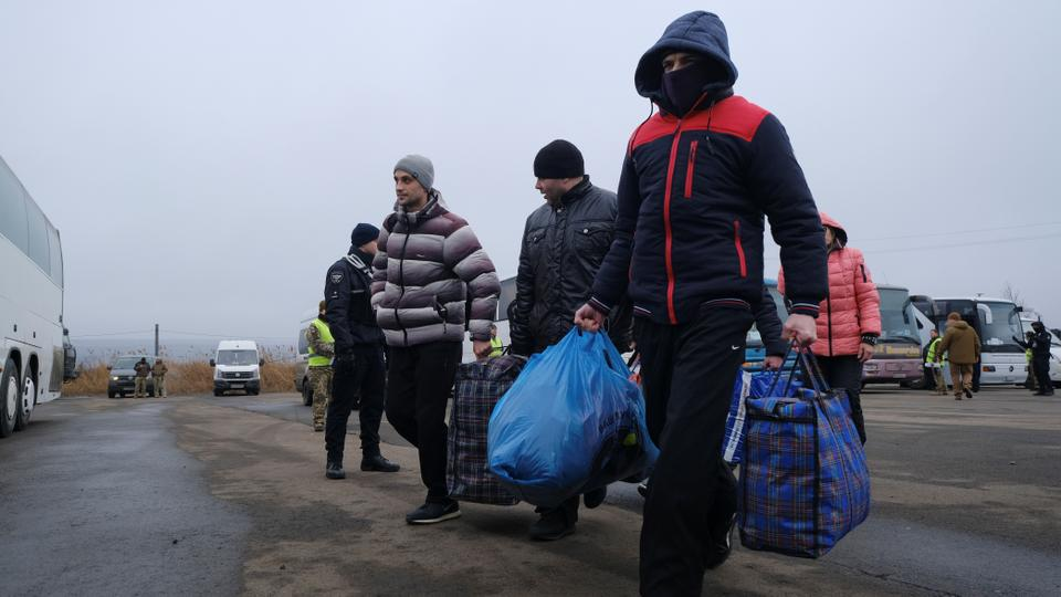 Men walk before reuniting with servicemen and officials of the self-proclaimed republics during the exchange of prisoners of war (POWs) between Ukraine and the separatist republics near the Mayorsk crossing point in Donetsk region, Ukraine on December 29, 2019.