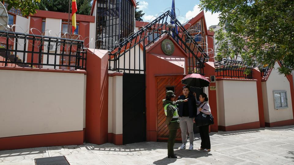 A police officer speaks with two persons in front of the Spain's embassy in La Paz, Bolivia on December 30, 2019.