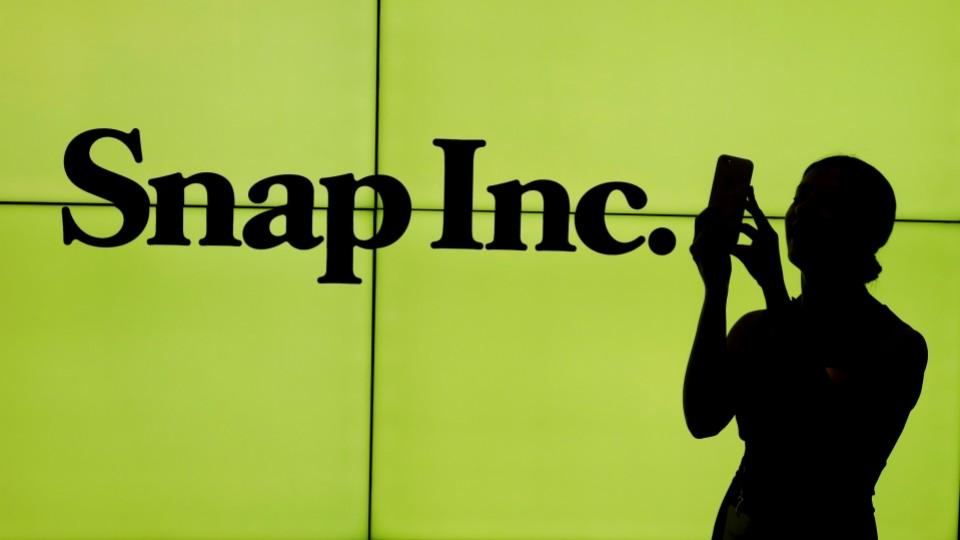 A woman in front of the Snap Inc logo on the floor of the New York Stock Exchange (NYSE) while waiting for Snap Inc to post its IPO, in New York City, on March 2, 2017.