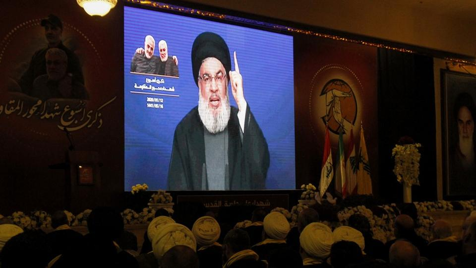 Supporters of Hezbollah watch as the group's leader Hasan Nasrallah delivers a speech on a screen in the southern Lebanese city of Nabatieh on January 12, 2020.