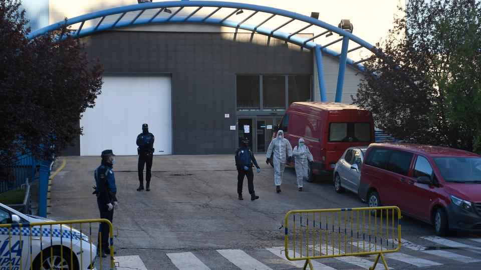 Policemen and members of the Spanish Army's Military Emergency Unit (UME) wearing protective suits stand outside the Palacio de Hielo (Ice Palace) shopping mall where an ice rink was turned into a temporary morgue on March 23, 2020 in Madrid to deal with a surge in deaths in the Spanish capital due to the coronavirus.