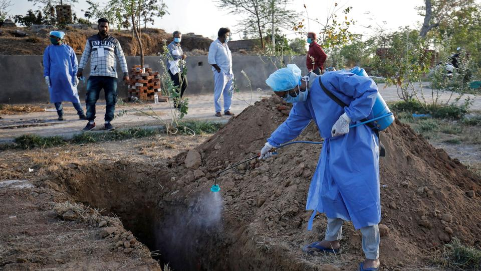 A municipal worker in Ahmedabad, India sprays disinfectant solution inside a grave before the burial of a woman who died of Covid-19 on March 28, 2020.