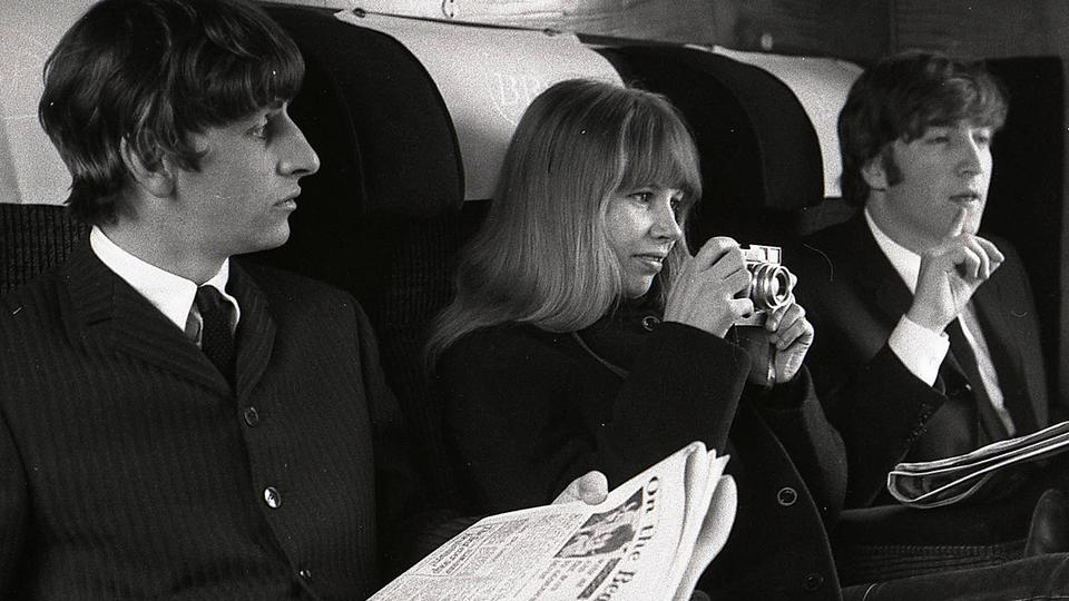 Astrid Kirchherr, poses with Ringo Starr and John Lenon on a train in 1960's. (Source: Twitter)