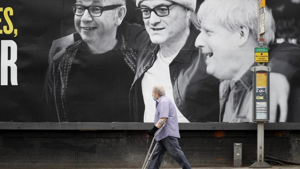 Bir yüz maskesi takan bir adam, (LR) İngiltere'nin Lancaster Dükalığı'ndaki Şansölyesi Michael Gove, 10 numaralı özel danışman Dominic Cummings ve İngiltere Başbakanı Boris Johnson'ın yer aldığı ve Kentish Town'daki siyasi kampanya grubu 'Eşekler Tarafından Led' başlıklı bir panoyu geçiyor. kuzey batı Londra 3 Haziran 2020'de.