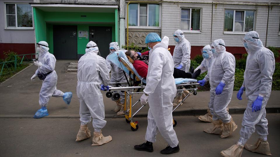 Sağlık görevlileri ve kişisel koruyucu ekipman (KKD) giyen Acil Durumlar Bakanlığı üyeleri, 28 Mayıs 2020, Tver şehrinde koronavirüs hastalığı (COVID-19) salgını ortasında bir hastayı taşırken sedye kullanıyorlar.
