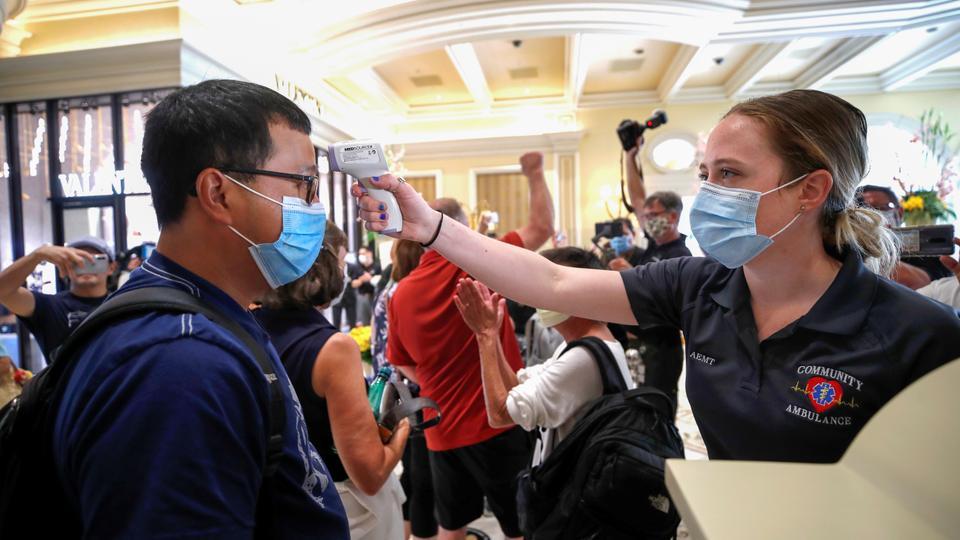 Bir tıp işçisi, 4 Haziran 2020'de Las Vegas, Nevada'da, koronavirüs hastalığının yayılmasını yavaşlatma adımlarının bir parçası olarak 16 Mart 2020'den beri kapalı olan Bellagio otel kumarhanesinin yeniden açılması sırasında gelen bir misafirin sıcaklığını kontrol ediyor.