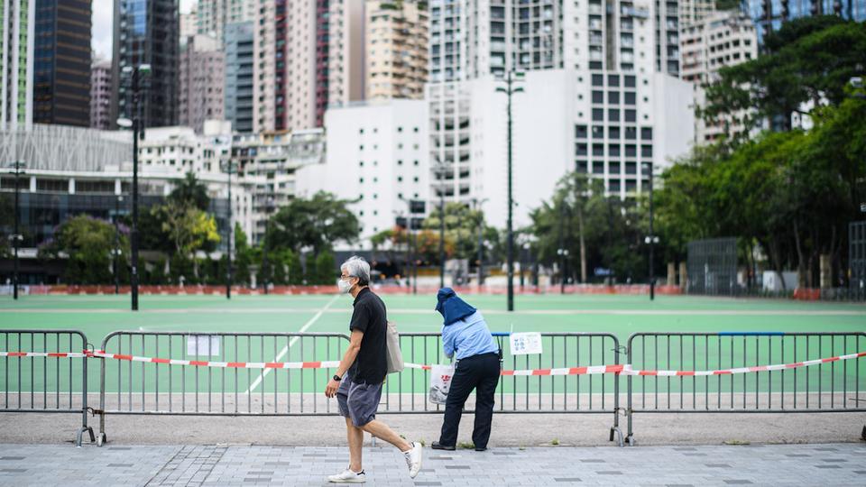 Bir adam, 4 Haziran 2020'de Hong Kong'daki barikatlı bir Victoria Park bölgesinde grup toplantılarına karşı insanları hatırlatan bir sayfa gösteren bir işçinin yanından geçer.